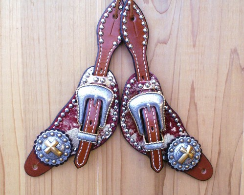 Small spur straps with red acid hide, cross conchos, and gold rope edge buckle sets